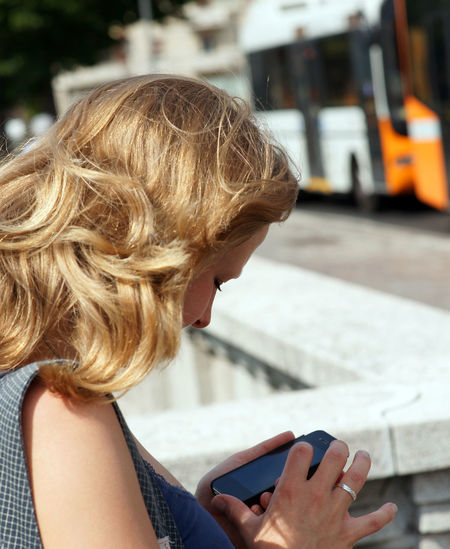 Close-up of woman with blond hair using smart phone in city