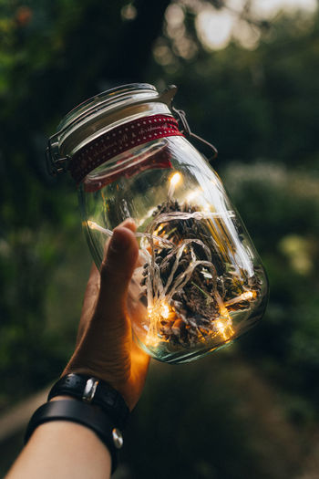 Cropped Image Of Hand Holding Glass Jar With Illuminated Lights