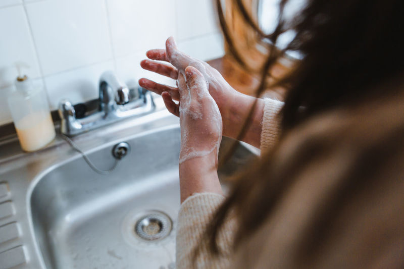 Midsection of woman in bathroom at home