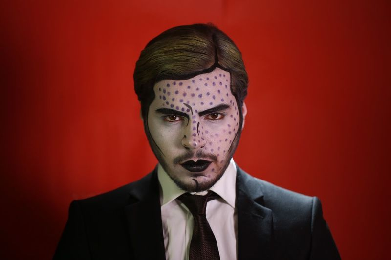 Close-Up Portrait Of Man With Halloween Make-Up Against Red Background