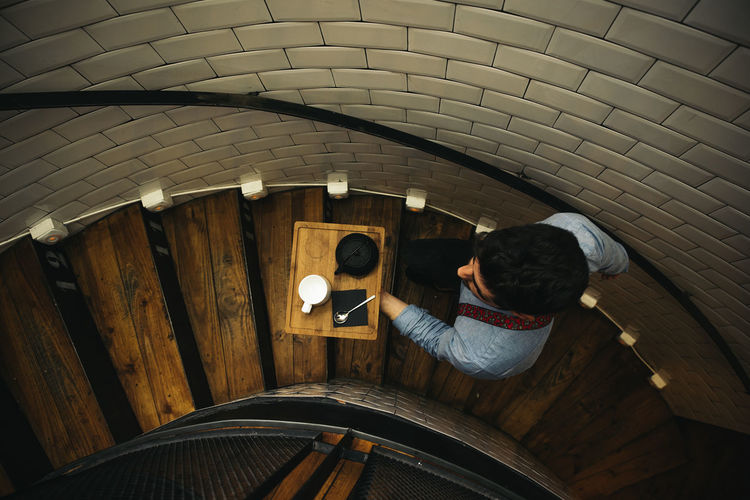 High Angle View Of Waiter With Tray Moving Up On Steps In Restaurant