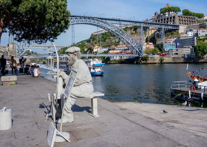 2017-05-04 sitting and white painted street artist, at Ribeira boulevard in Port. Along river Douro near famous Eiffel designed Dom Luiz iron bridge. Architecture Bridge - Man Made Structure Day Dom Luiz Bridge Douro  Eiffel Bridge Iron Bridge Luiz I Bridge Porto Portugal Promenade Real People Ribeira River Riversite View Sky Street Artist Water