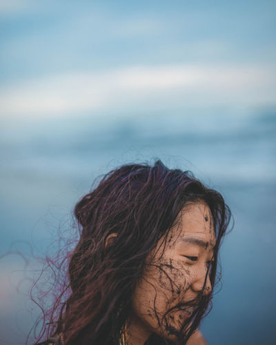 Portrait of woman against sea with sky in background