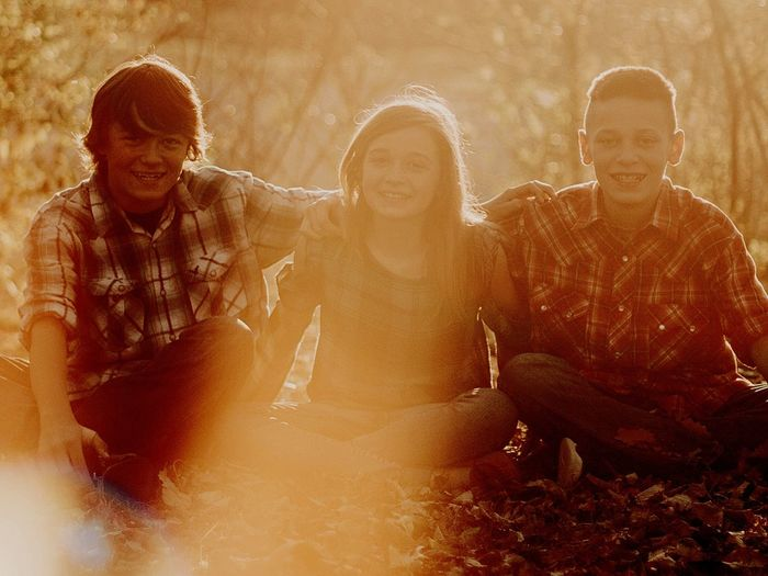 Portrait Of Siblings Smiling While Sitting On Field During Sunset