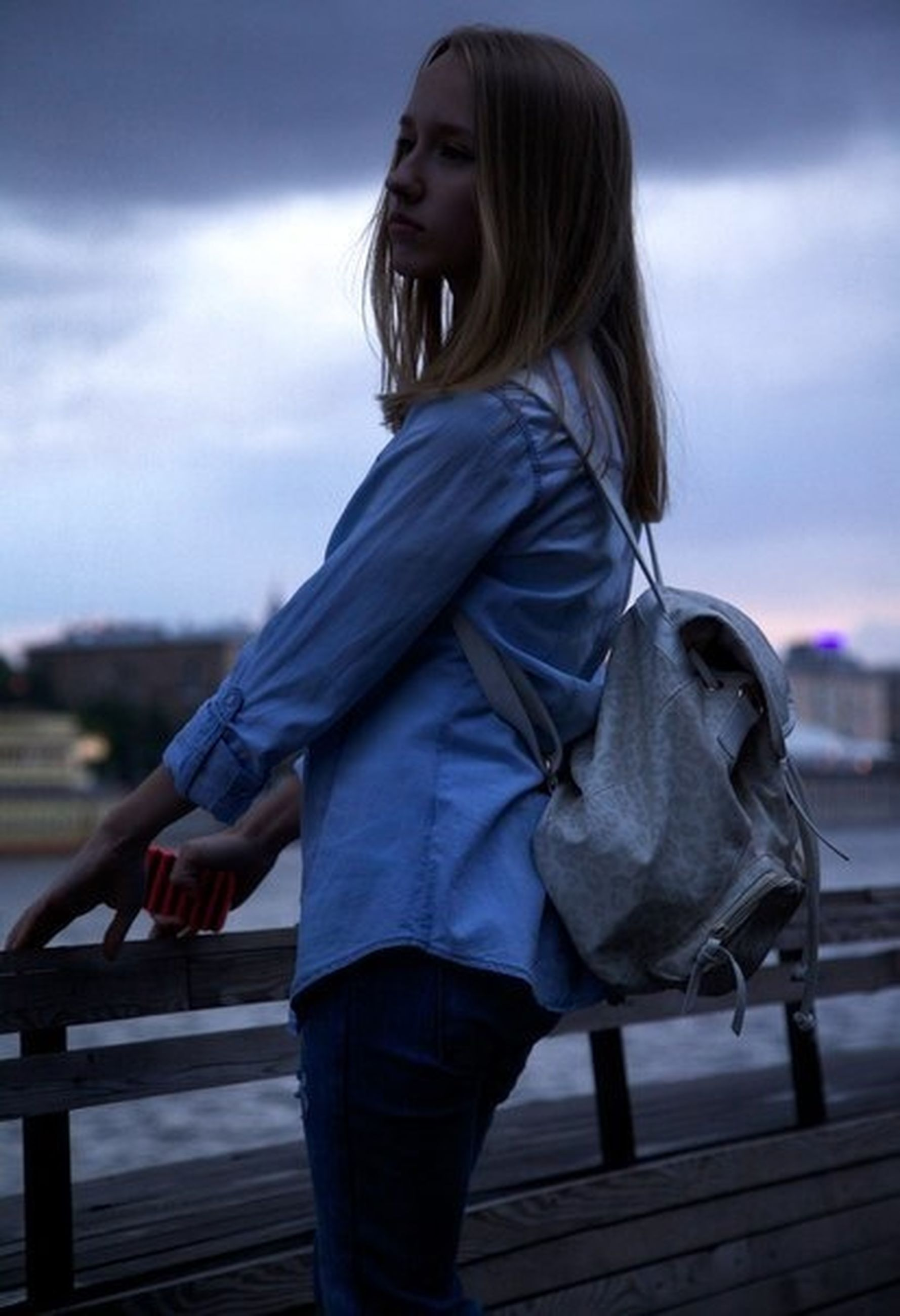 focus on foreground, railing, lifestyles, sky, casual clothing, standing, leisure activity, rear view, side view, three quarter length, looking away, outdoors, young adult, day, cloud - sky, full length, cloud, waist up
