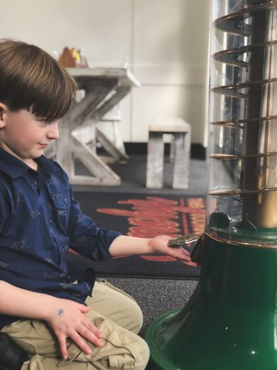 Boy looking at equipment while kneeling at cafe