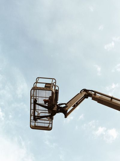 Low angle view of cherry picker against sky