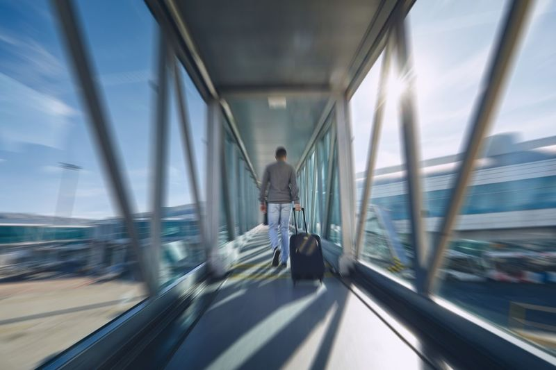 Man hurrying at airport. Rear view of passenger with luggage walking to terminal. Men Travel Airport Airport Terminal Leaving Speed Motion on the move Rush Urgency Delay Blurred Motion Passenger People One Person Transportation Walking Running Passenger Boarding Bridge Luggage Suitcase Time Emotional Stress Flying Fast