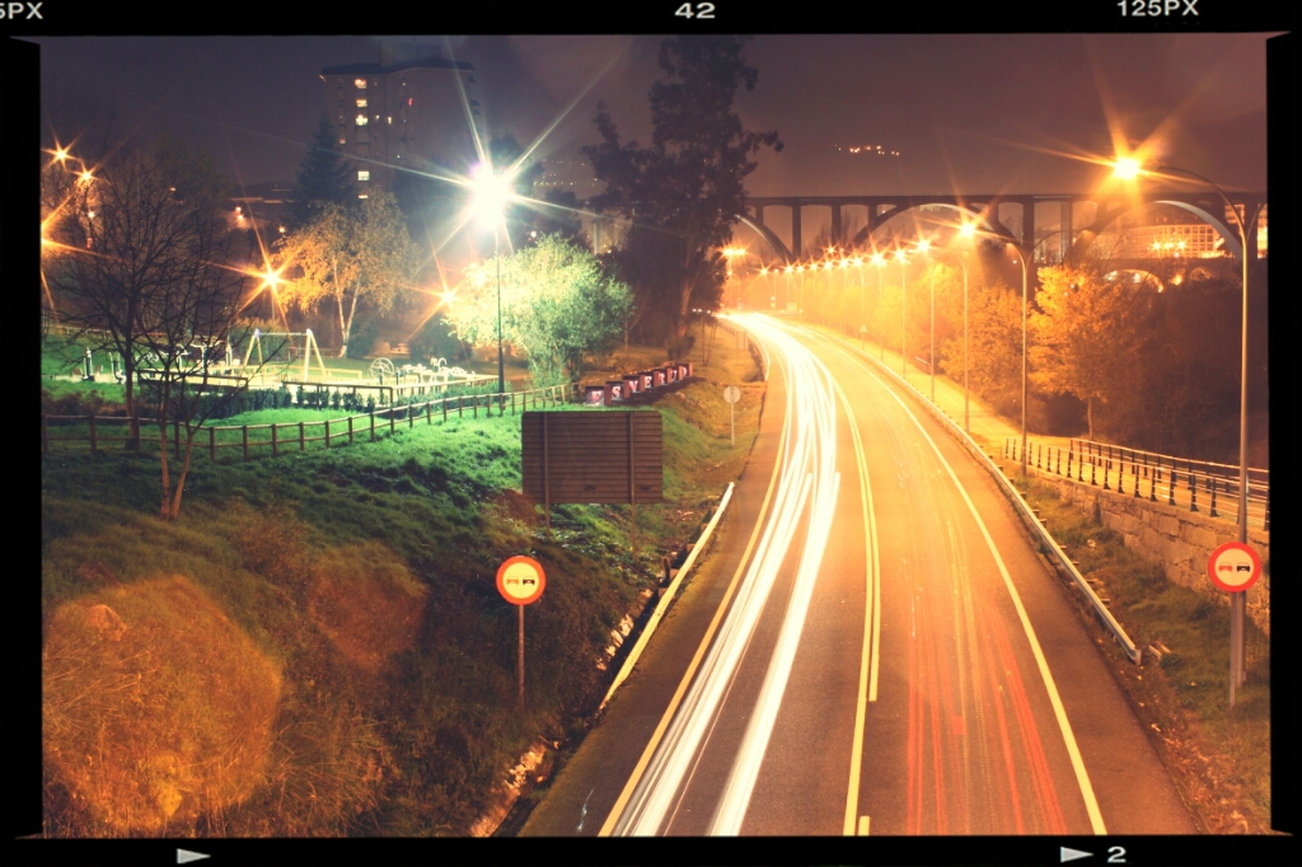 illuminated, night, transportation, light trail, street light, long exposure, railroad track, road, the way forward, speed, motion, city, high angle view, transfer print, blurred motion, auto post production filter, diminishing perspective, street, lighting equipment, vanishing point