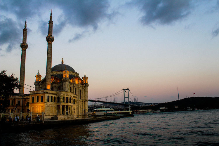 Mosque by strait against cloudy sky during sunset