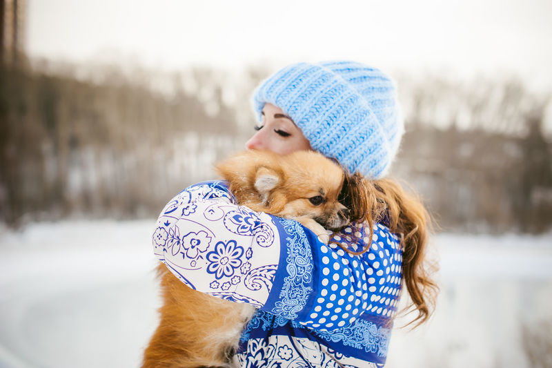 Woman With Puppy Standing On Snow Against Sky During Winter