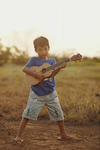 Full length of boy standing on field playing ukulele