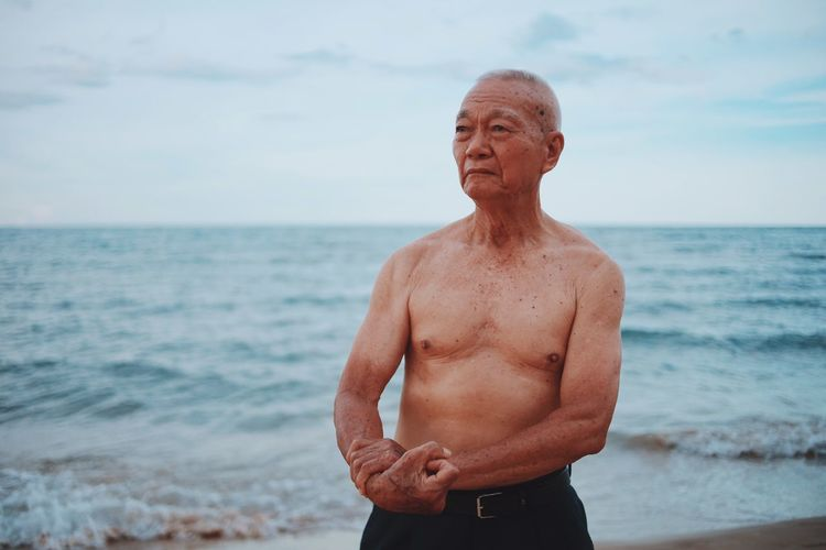 Shirtless senior man showing muscles while standing at beach against sky during sunset