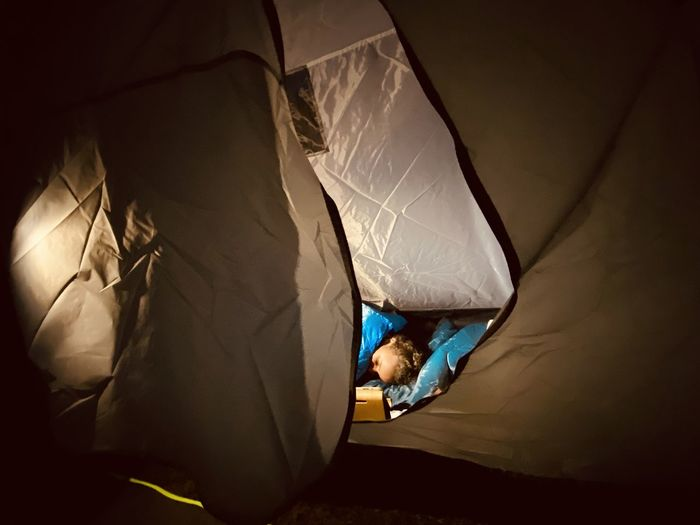 High angle view of girl sleeping in tent