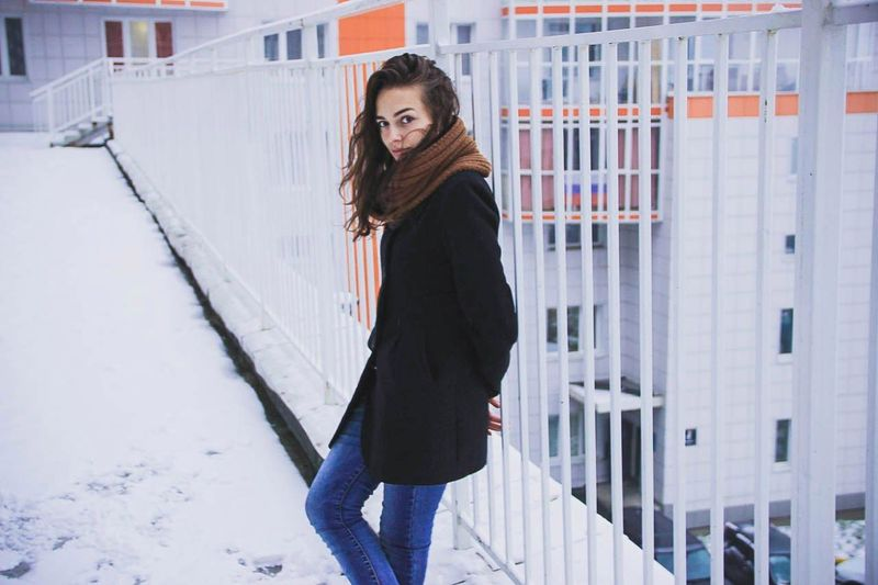 Portrait of young woman standing bu railing in snow