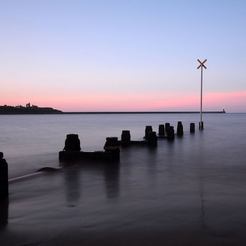 Wooden Posts In River Against Sky During Sunset