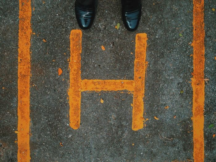 Black shoes by yellow letter h on road