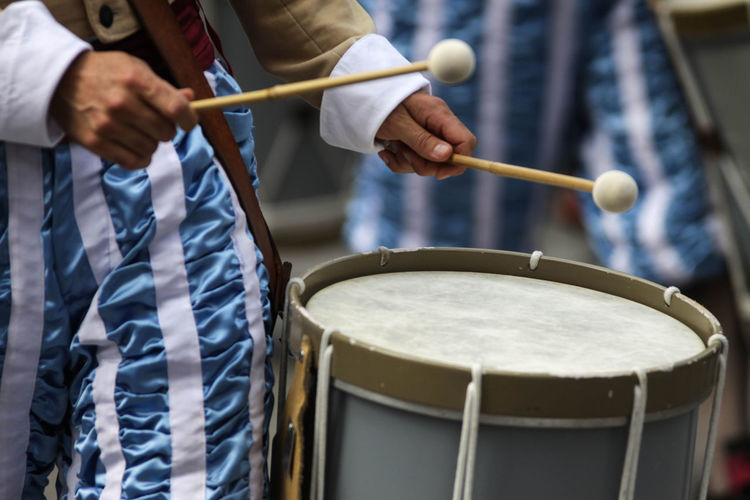 Midsection of man playing drum in city