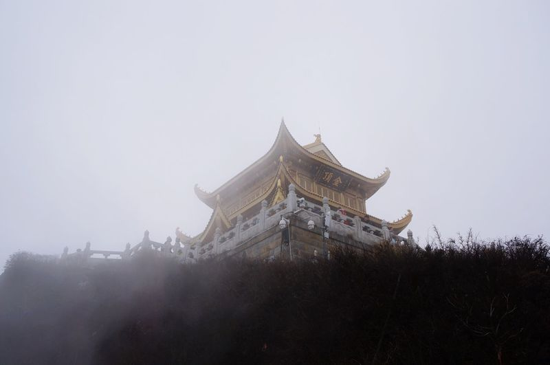 Low Angle View Of Golden Summit Temple Against Sky During Foggy Weather