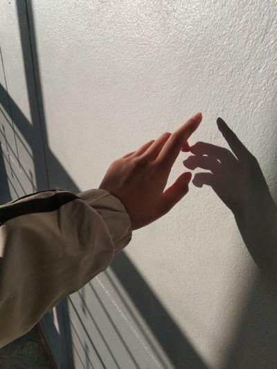 Cropped image of hand touching wall