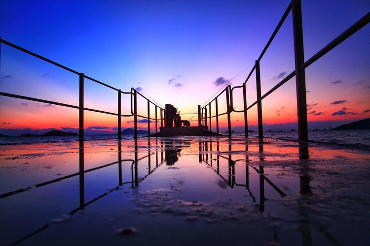 Silhouette Railing On Shore At Beach Against Dramatic Sky During Sunset