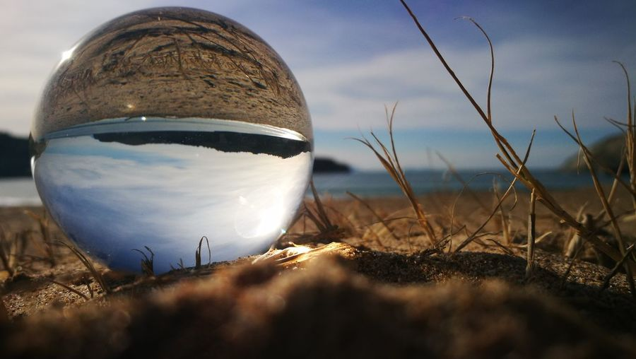 Close-up of glass ball on beach against sky