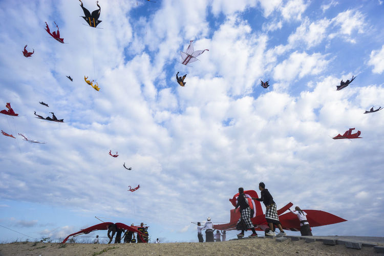Low angle view of people flying kites against cloudy sky