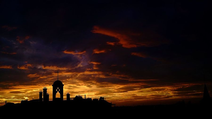 Silhouette of building against sunset sky
