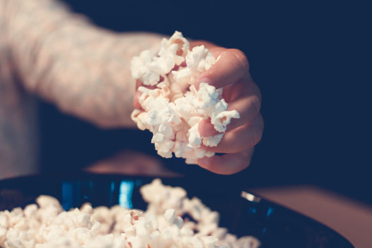 Cropped hand of person picking popcorn from bowl
