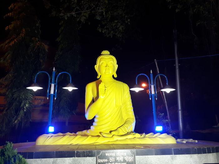 Statue of illuminated buddha at night