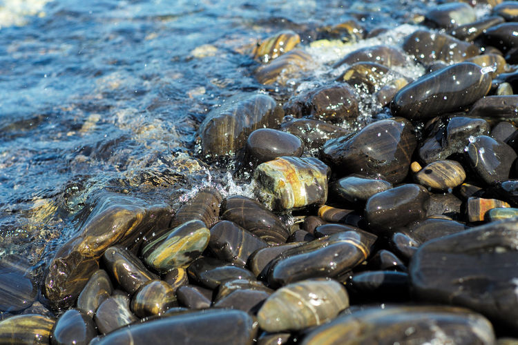 Close-up group of polished stones on beach surfed by the sea