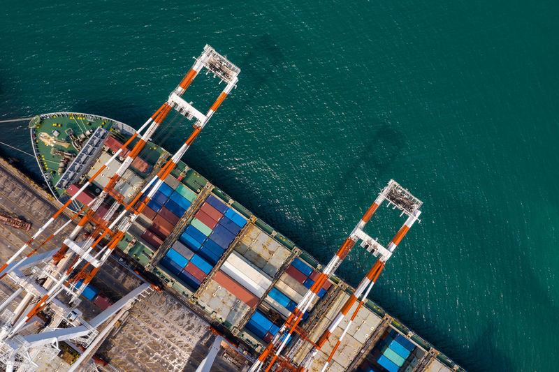 High angle view of commercial dock and containers ship with crane loading unloading in thailand