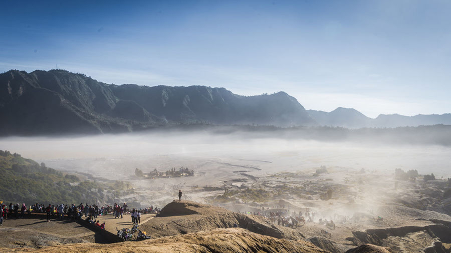 Group of people on landscape against mountain range during foggy weather
