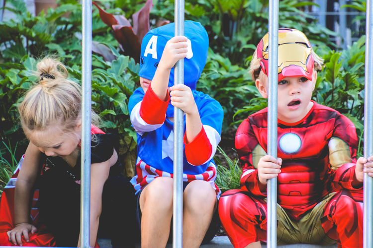 Superhero Boys Child Childhood Costume Day Females Friendship Girls Group Of People Holding Innocence Leisure Activity Lifestyles Males  Outdoors People Real People Sitting Three Quarter Length Togetherness