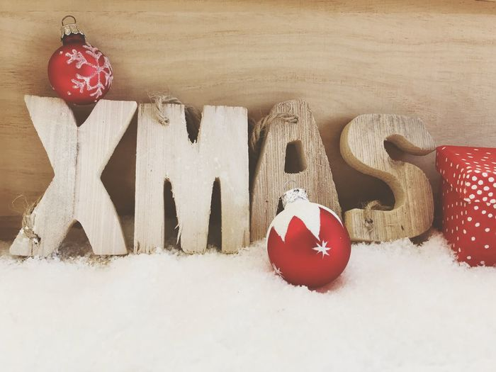 Close-up of christmas decorations on snow against wall