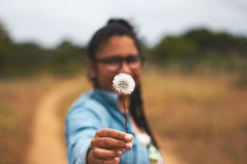 Close-up of woman holding dandelion on field