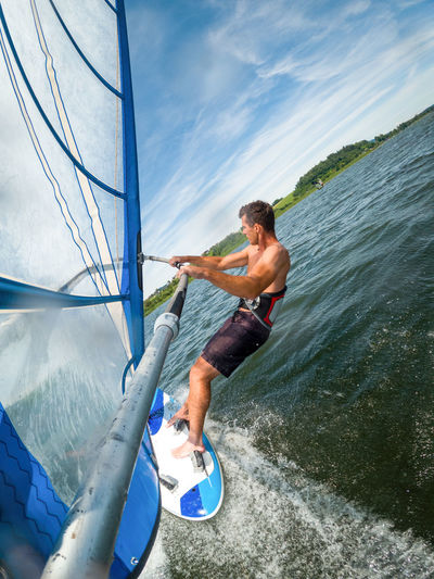 Wide-angle shot of adult man windsurfing on lake wallersee, austria.