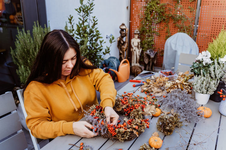 Woman making wreath while sitting by table at shop