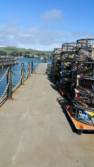 Crab cages on the docks Crabbing Crab Cages Crabbing Industry Background Dock Cables Bay Sea Copy Space Red Yellow Industry Living Work Job Trappings Stacked Piles Rows Lines Lined Up Multiple Many Water Sea Beach Pier Sky Horizon Over Water