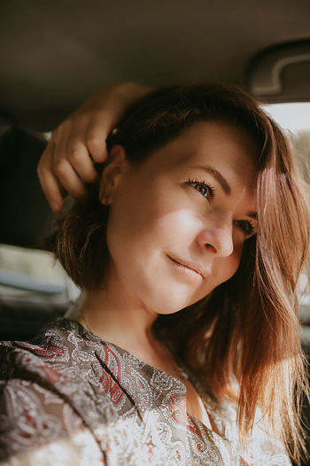young woman with dark short hair and silver earrings sitting in the car at the window