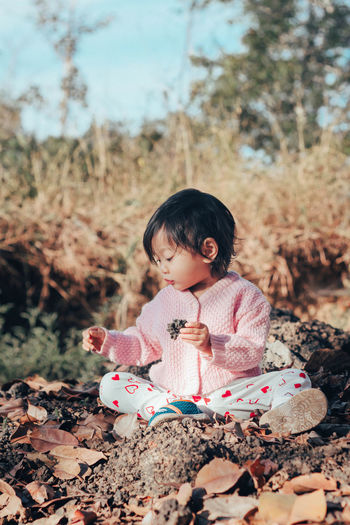 Cute baby girl looking at stone while sitting on land