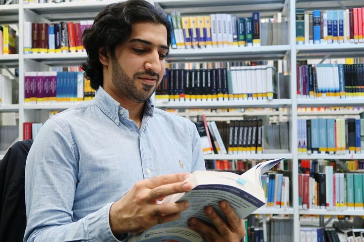 Mid Adult Man Reading Book In Library