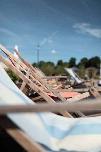 Close-up of deck chairs on table against sky