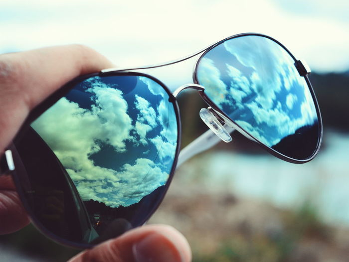 Close-up of hand holding sunglasses against sky