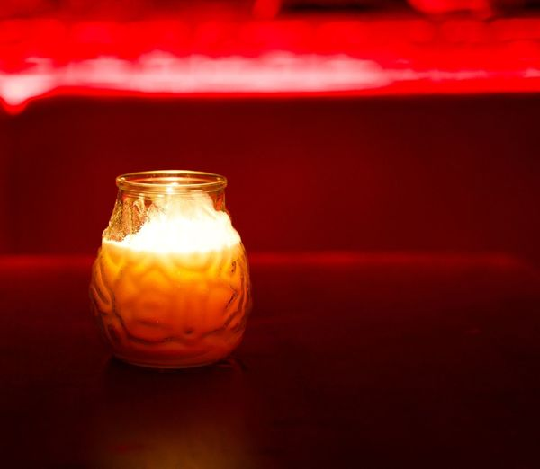 Red Wax Candle in Glass against red bokeh background. Concept of harmony, balance and meditation, spa, relax. Red Indoors  No People Close-up Single Object Illuminated Wax Wax Candle Bokeh Background Harmony Balance Meditation Springtime Relaxing Relaxation Glass Red Wax Cherries