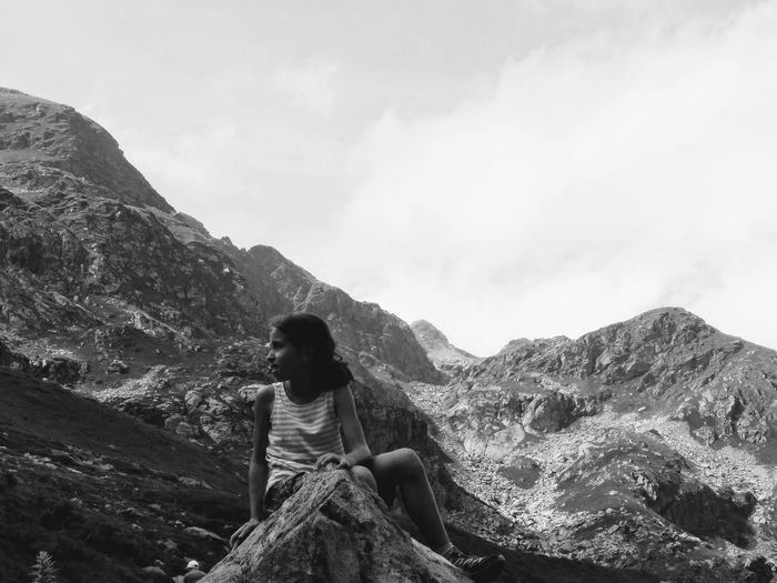 Low angle view of girl looking away while sitting on rock against mountain
