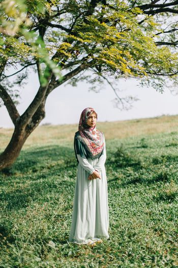 Woman standing on field against tree
