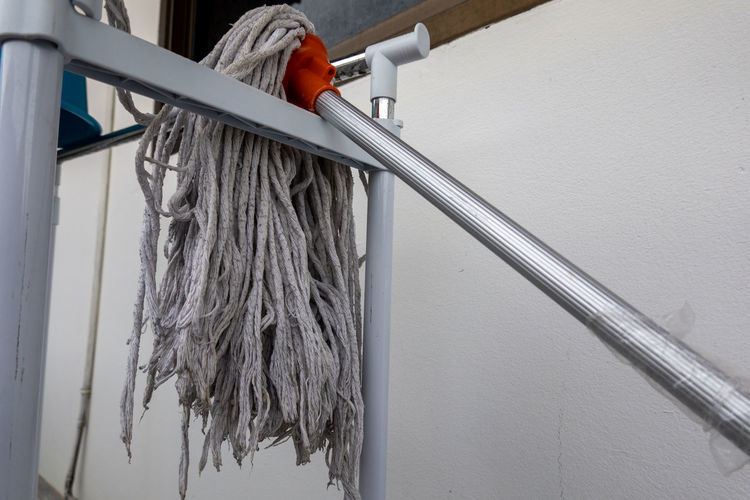 Low angle view of rope hanging on metal wall