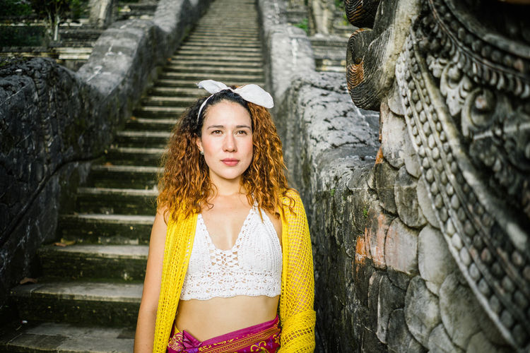 Architecture Beautiful Woman Beauty Built Structure Contemplation Day Front View Hair Hairstyle Leisure Activity Lifestyles Long Hair Looking At Camera One Person Outdoors Portrait Staircase Standing Stone Wall Teenager Waist Up Women Young Adult Young Women