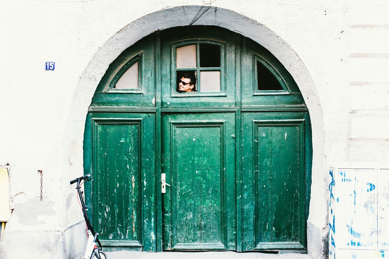 door, entrance, architecture, built structure, building exterior, closed, day, security, building, green color, protection, safety, no people, wall, window, house, outdoors, wood - material, wall - building feature, arch, turquoise colored, window frame